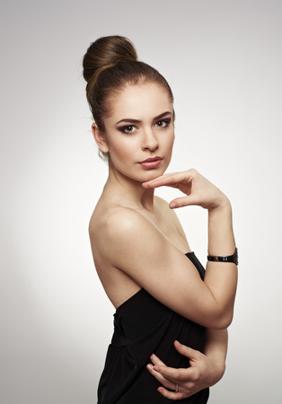 'retro styled': Portrait of glamor fashion model with stylish hairdo posing in studio. Young attractive Caucasian female wearing black dress . Stock Photo
