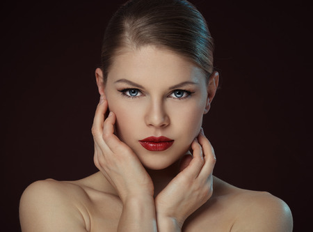 woman face cream: Lovely young female touching her clean face over black background. Close-up portrait of Caucasian fashion model with professional makeup and hairstyle posing in studio.