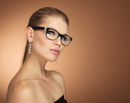 specs: Fashion portrait of young glamour female in optical eyewear with black frame over golden background. Pretty girl with beautiful evening makeup wearing jewelery posing in studio.