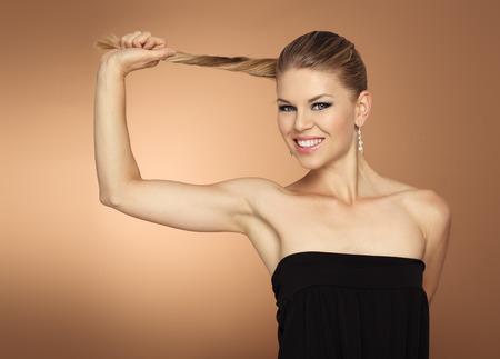 cola mujer: Retrato del estudio del modelo de mujer con su larga cola feliz sonriendo. El cabello sano termina concepto. Foto de archivo
