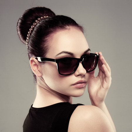 sunglasses: Primer plano de la hermosa modelo morena en elegantes gafas de sol negras. Hembra bonita joven con peinado retro posando en el estudio.