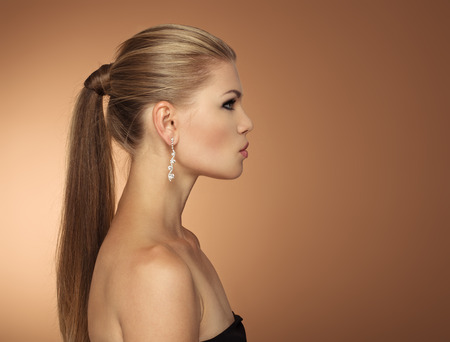 women hair: Portrait of fashionable young woman with long hair tail in profile. Serious elegant female wearing jewelery looking aside at space for text.