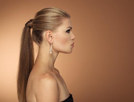 capelli lunghi: Ritratto di moda giovane donna con lunghi capelli coda di profilo. Grave donna elegante indossare gioielli che osserva da parte a spazio per il testo.