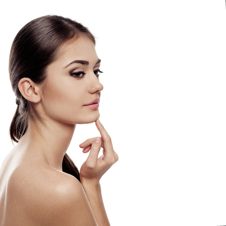 collagen: Close-up portrait of young woman applying cream isolated over white . Facial care, therapy and protection concept. Stock Photo