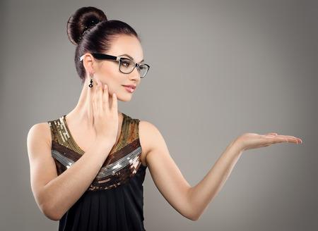 Beautiful brunette girl in eyewear showing something. Young attractive Caucasian woman model in stylish dress wearing optical eyeglasses. Standard-Bild