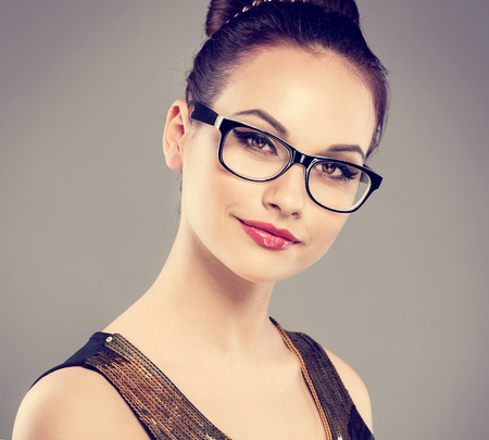 メガネをファッションのグラマー モデルのクローズ アップの肖像画。若い魅力的な白人女性スタジオ カメラ目線でポーズします。 写真素材
