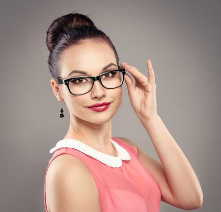 眼鏡のプロの髪型とファッショナブルなブルネットの女性のクローズ アップの肖像画。めがねスタジオでポーズをとる若い美しい女性モデル。