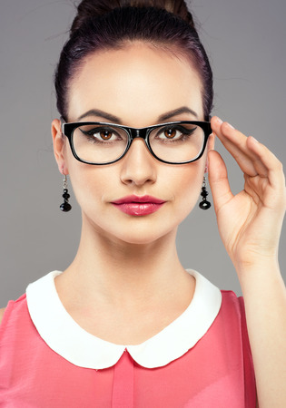 Studio shoot of young pretty female brunette touching her optical eyeglasses. Portrait of retro styled girl with professional make-up and hairdress.