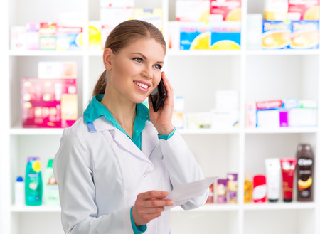 medical assistant: Portrait of female pharmacist consulting customer on phone holding recipe. Young woman medical assistant in pharmacy.