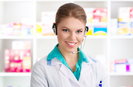 druggist: Close-up of young woman pharmacist chemist servicing customer on phone. Happy smiling female druggist wearing headset standing in drug shop.