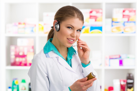 druggist: Female druggist consulting customer on phone in pharmacy. Young pretty drug store worker holding bottle with pills. Stock Photo