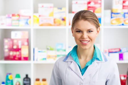 Young salesperson in drug store posing over medicines background. Happy smiling woman pharmacist in labcoat servicing customers. Stock Photo