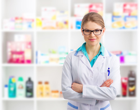 Portrait of confident woman pharmacist wearing uniform selling medicines and cosmetics in her retail shop. Banque d'images