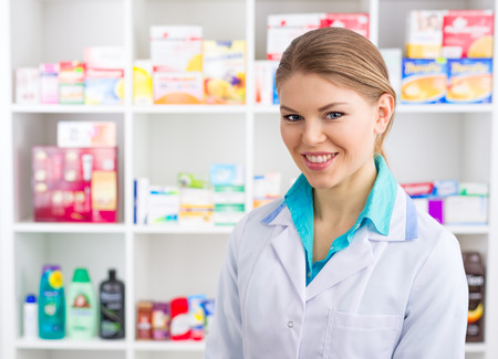 intern: Close-up of smiling medical assistant servicing customers in drugstore. Young female intern in labcoat selling pharmaceuticals.