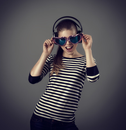 funny picture: Funny picture of clubbing girl wearing headphones and heart shaped eyeglasses. Young cheerful Caucasian woman in motion posing in studio.