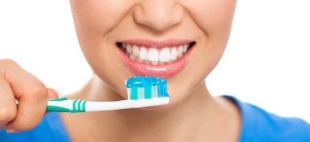 dientes: Los dientes sanos y un aliento concepto. Retrato del primer de la mujer feliz que limpia sus dientes con pasta de dientes sobre fondo blanco.