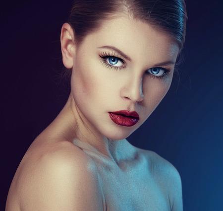 어두운 배경 위에 전문 메이크업과 복고풍 붉은 입술을 가진 패션 모델. 웰빙 및 얼굴 케어 개념입니다.