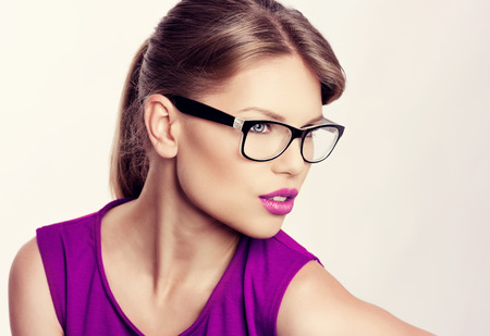 purple dress: Close-up portrait of beautiful young blonde wearing stylish eyeglasses with purple lips. Attractive Caucasian businesswoman in spectacles. Stock Photo