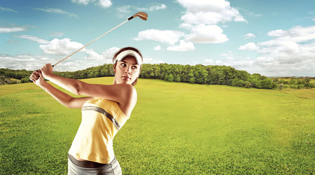Young female golf player swinging with golf club outdoors. Woman in sportswear playing golf on green field over beautiful landscape background. Banque d'images