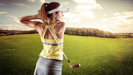 Young female in sportswear playing golf on green field. Active fresh Caucasian woman swinging with golf club. Archivio Fotografico