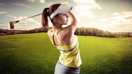 Femme énergique pratiquer exercice de golf sur le magnifique paysage de fond. Jolie sportive de frapper la balle avec un club de golf. Banque d'images