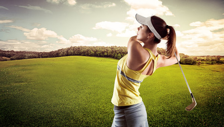 Sporty young female playing golf on the nature. Active girl in sportswear golfing in green field. Banque d'images