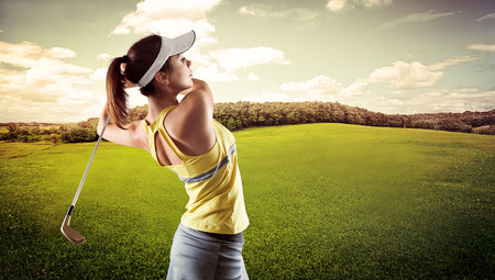 Portrait of energetic Caucasian girl doing swing on course at the summer. Focused woman with driver playing luxury game Stock fotó