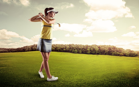 Active female player preparing for hitting golf ball. Young sporty girl looking at ball course on green field.