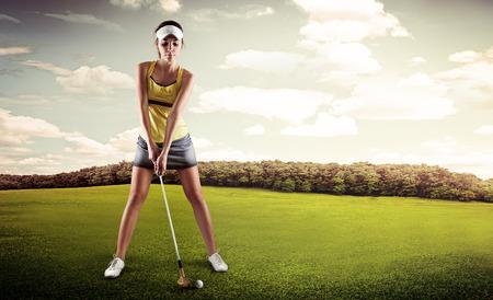 Portret van vrouwelijke golfer met golf club teeing-off op de natuur. Jonge sportieve vrouw speler stond in golf positie klaar voor hit. Stockfoto