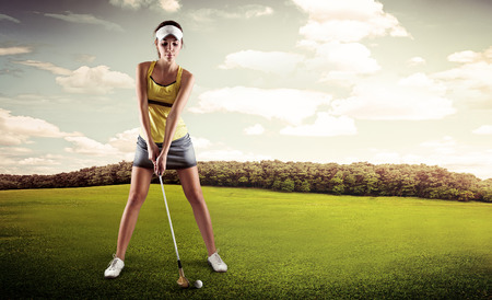 Portrait of female golfer with golf club teeing-off on the nature. Young sporty woman player standing in golf position ready for hit.