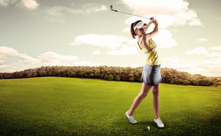 Active woman player hitting the ball on golf court. Sporty female exercising golf play on nature over beautiful landscape background.