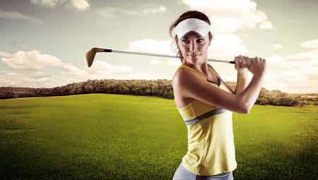 golf swings: Close up portrait of pretty smiling woman standing with golf club outdoors. Young female golf player wearing sportswear swinging on green field.
