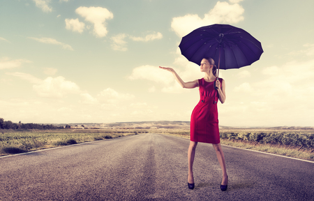 sun umbrella: Crisis behind. Protection concept. Beautiful young businessperson standing with umbrella over cloudy sky background. Stock Photo