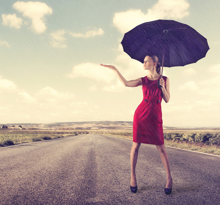Pretty young business woman standing with umbrella in the rain. Concept of crisis protection and risk insurance.