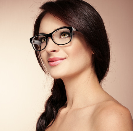 Portrait of pretty brunette model in fashionable spectacles. Young beautiful smart lady wearing stylish eyeglasses posing in studio.