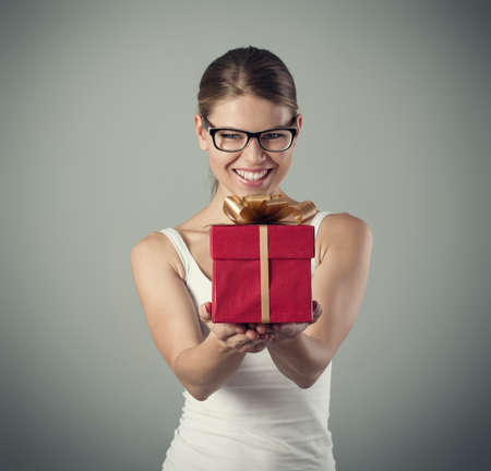 congratulating: Winner gift concept. Close-up studio portrait of young attractive woman congratulating somebody with triumph. Stock Photo