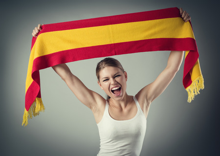 flag of spain: Excited young woman football fan cheering with Spanish flag celebrating victory of favorite team. Stock Photo