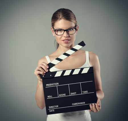film director: Portrait of pretty woman holding clapperboard. Film production and movie making concept.