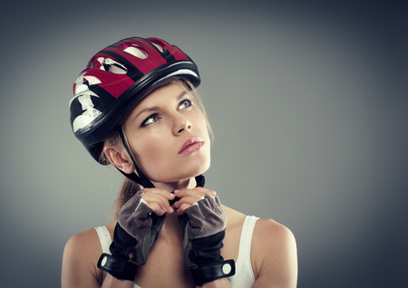 cycling helmet: Cycling. Woman putting biking helmet before ride. Portrait of young female athlete professional sportswoman.