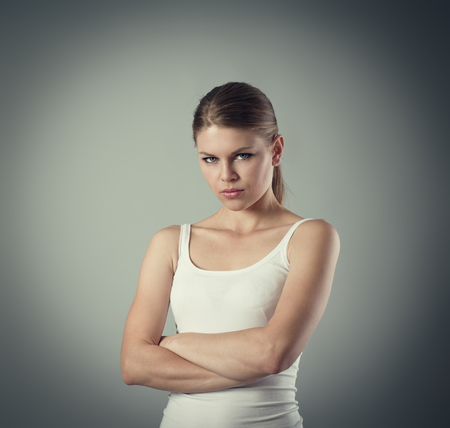 sullen: Studio portrait of sullen woman over grey background. Young aggressive Caucasian female standing with crossed arms. Stock Photo