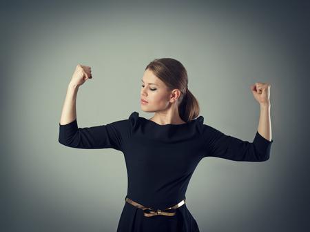 Krachtig en sterk zakenvrouw concept. Jonge vrouw in jurk op zoek naar haar gespierde armen poseren in de studio.