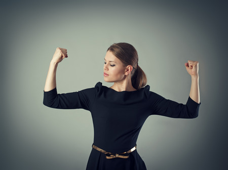 winning business woman: Powerful and strong business woman concept. Young female in dress looking at her muscled arms posing in studio.