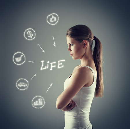 Portrait of young pensive female thinking of life priorities and duties. Focused woman standing with crossed arms looking at drawn lifestyle chart.