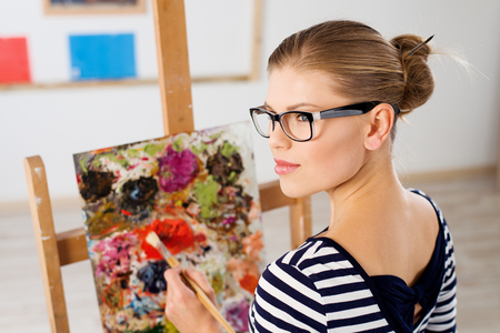 artist: Pretty woman painting with brush and acrylic paints in artistic studio. Pensive female standing at easel with colorful picture.