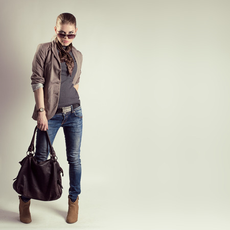 Portrait of gorgeous fashion woman in sunglasses holding stylish leather bag. Young beautiful Caucasian female model wearing fashionable jeans, jacket and high heels shoes.