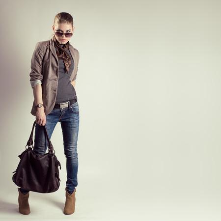 Portret van prachtige mode vrouw in zonnebril met stijlvolle lederen tas. Jonge mooie Kaukasische vrouwelijke model draagt modieuze jeans, jas en hoge hakken schoenen.
