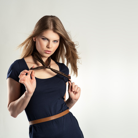 neckerchief: Portrait of seductive elegant model in fashionable dress posing in studio. Beautiful blonde stylishly dressed touching her neckerchief. Stock Photo