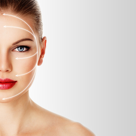Skin care and rejuvenation therapy on pretty woman face. Close-up portrait of attractive Caucasian female model with red lips isolated over white background. Stockfoto