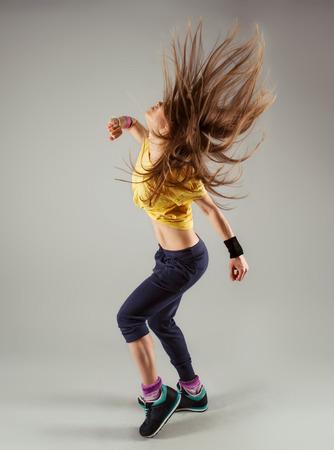 Jonge energieke fitness vrouw danser te bewegen in de klas. Mooie slanke vrouwelijke artiest in beweging.