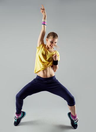 Gelukkig meisje uitwerken dans zich met hand up. Dynamische vrouw fitness trainer dansen voor de lol. Stockfoto